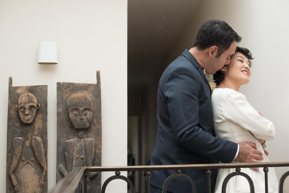 Photo de couple de mariés avec une statue en bois