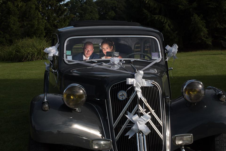 Photos de mariée dans une voiture de collection avec lumière créative de jour au Domaine de la Butte Ronde