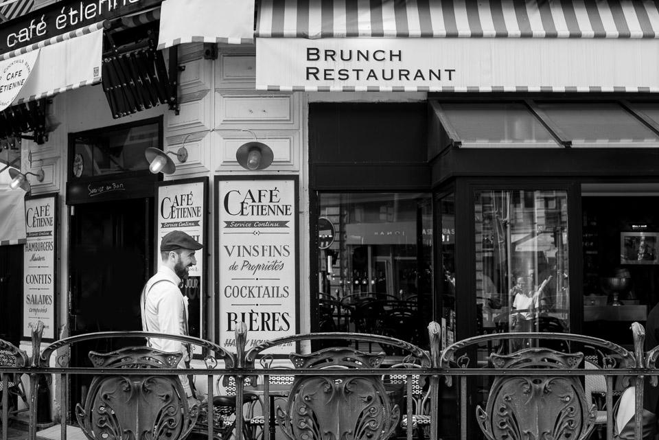 Photo en noir et blanc d'un marié devant un bistro parisien