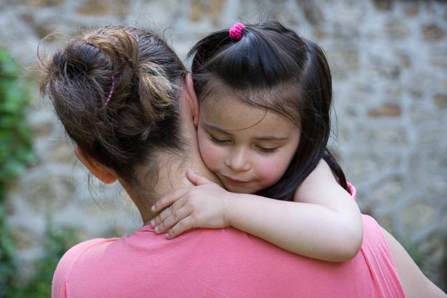 Petite fille avec sa tête sur l'épaule de sa maman